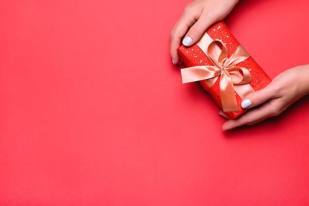 빨간색 배경, 카피스페이스에 황금색과 붉은 색으로 선물 상자를 들고 있는 여자. 트렌디한 색상의 발렌타인 데이 인사말 카드 또는 여성의 날 카드, 위쪽 전망, 해피 발렌타인 데이 배경 오버헤드