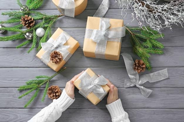 Женщина держит подарочную коробку на деревянном столе