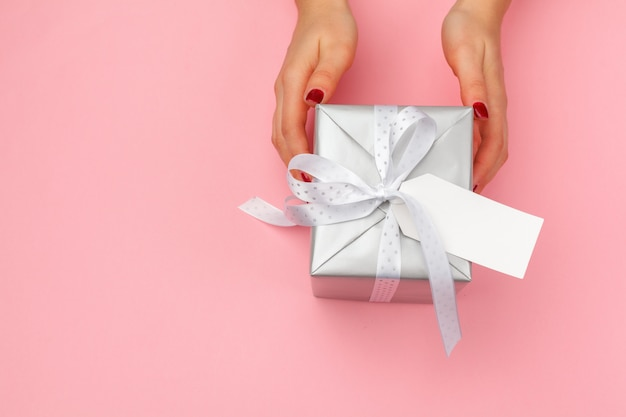 Woman holding gift box on pink