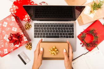 Woman holding gift box while shopping online at table with Christmas decoration