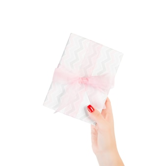 Woman holding a gift box with pink ribbon on white. flat lay