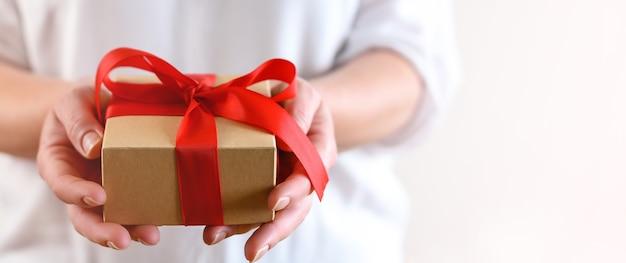 Женщина держит подарочную коробку с красным бантом