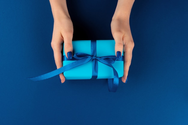 Woman holding gift box with ribbon against classic blue background, top view