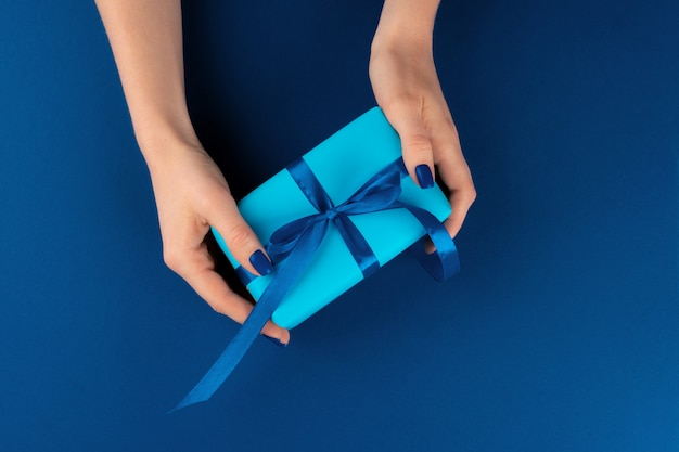 Woman holding gift box with ribbon