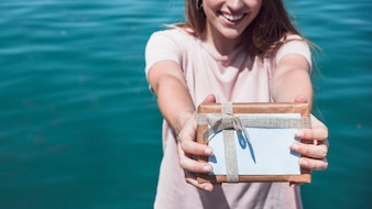 Woman holding gift in front of sea water background