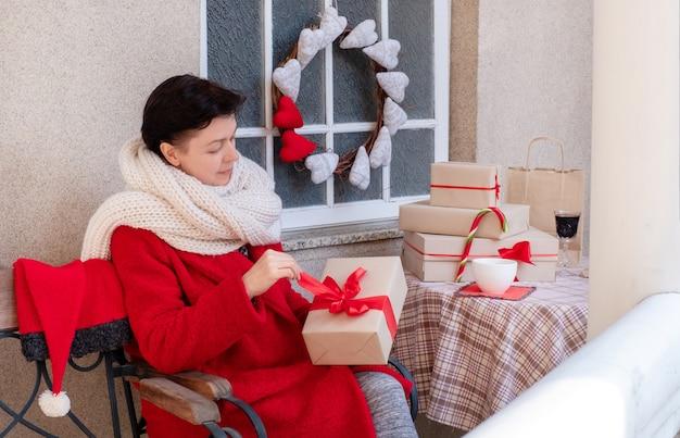 Женщина держит подарочную коробку с красным бантом накануне праздников рождества и нового года