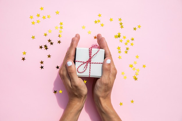 Woman holding gift and sparkles