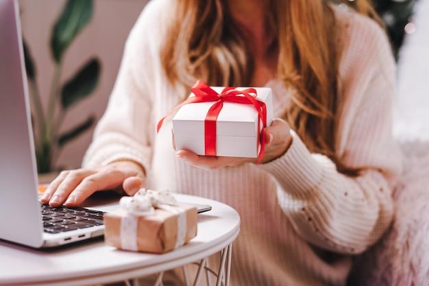 ノートパソコンでギフトタイピングを保持している女性。休日のオンラインショッピング