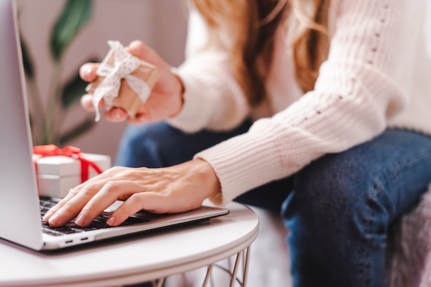 Woman holding gift typing at laptop. holidays online shopping