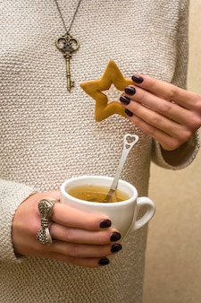 Woman holding ginger sweet cookie in hand with cup mug tea, festive christmas food dessert decor. xmas, new year decorations. winter holiday concept