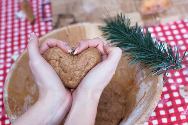 Woman holding gingerbread dough at hands in the shape of heart