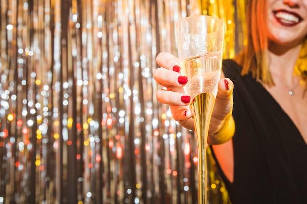 Женщина, держащая стакан на праздновании нового года