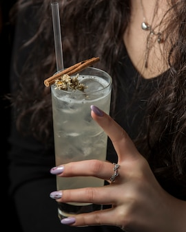 Woman holding glass of drink garnished with dried flower and cinnamon stick