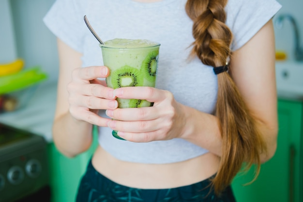 Woman holding glass of green smoothie of celery and banana in glass decorated with slices of kiwi. healthy vegan lifestyle