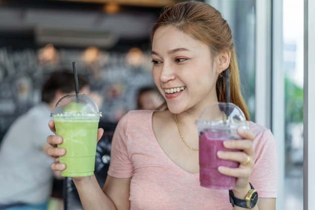 Woman holding glass of green tea frappe and blueberry smoothies