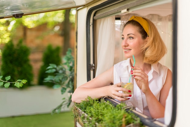 Woman holding a glass of lemonade in a caravan with copy space