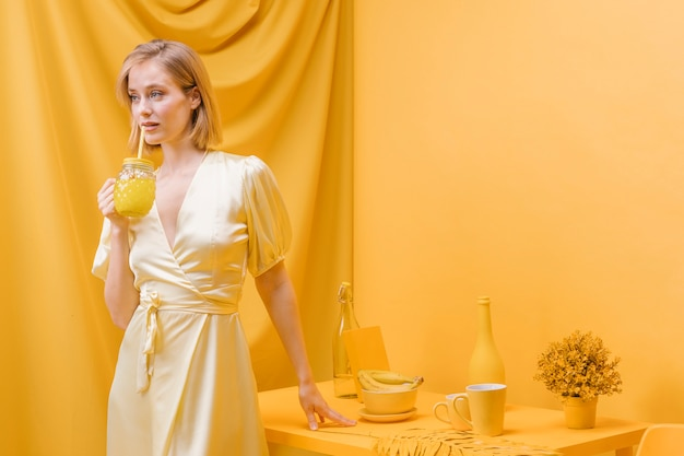 Woman holding glass of lemonade in yellow scene