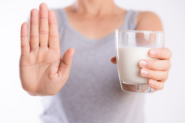 Woman holding glass of milk and another hand shows stop sign. health problem