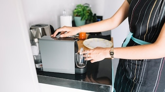 Woman holding glass mug under the coffee machine in kitchen