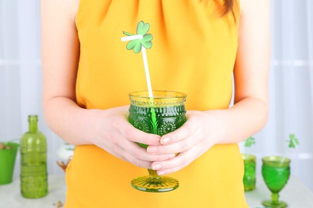 세인트 패트릭 데이에 클로버 잎과 음료 한 잔을 들고 여자