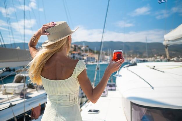 ポロスギリシャの港でヨットに対してグラスワインを保持している女性