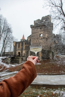 Woman holding a glass of wine on the background of a medieval castle in the snow