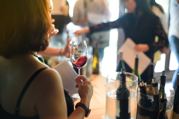 Woman holding a glass of wine at a party.
