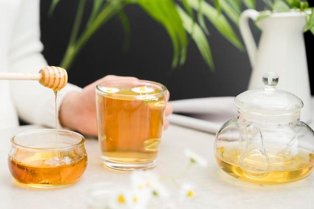 お茶と蜂蜜ディッパーでガラスを保持している女性