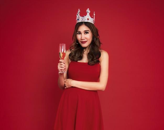 Женщина держит бокалы шампанского и улыбается во время празднования на красном фоне.