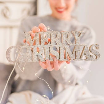 Woman holding glitter Merry Christmas inscription