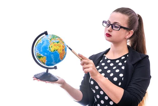 地球儀を保持し、白で隔離のそれを指している女性