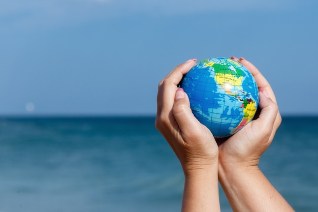 Woman holding globe of the earth on a background of the sea.