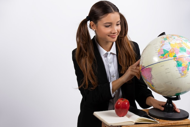 Woman holding globe looks at it near book apple white wall with space