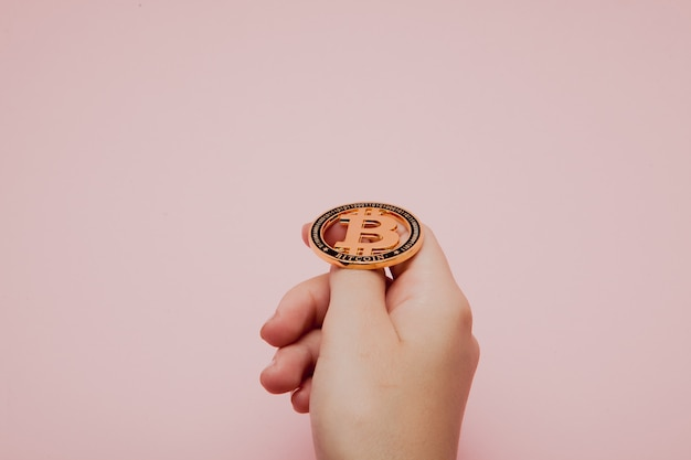 Woman holding glowing new gold bitcoin