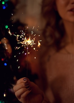 Woman holding glowing sparkler in party