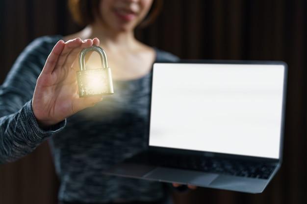 Женщина держа ключ замка золота мастерский с компьтер-книжкой концепция для того чтобы зафиксировать данные.