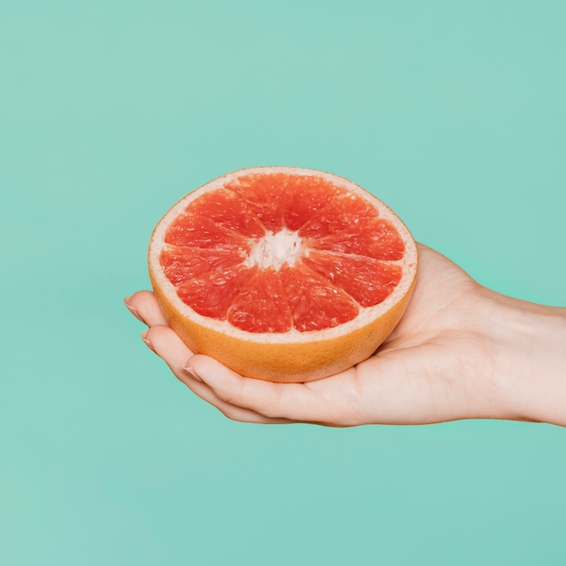 Woman holding grapefruit against a green background
