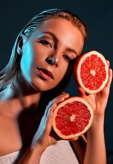 Женщина, держащая грейпфрут возле лица.