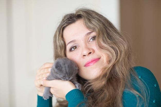 灰色のスコティッシュフォールドの子猫を保持している女性