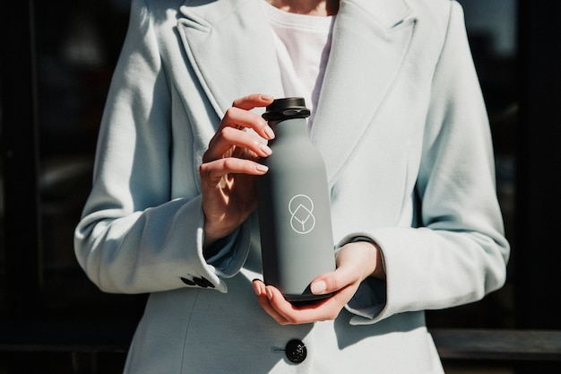 Woman holding a gray stainless steel bottle