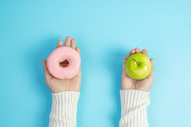 녹색 사과와 분홍색 도넛을 들고 있는 여성, 과일 중에서 선택하는 여성은 건강한 음식이고 달콤한 것은 건강에 해로운 정크 푸드입니다. 다이어트, 비만, 식습관 및 영양 개념