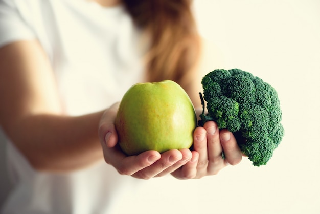 Woman holding green apple and broccoli in her hands. copy space. clean detox eating, vegetarian, vegan, raw concept
