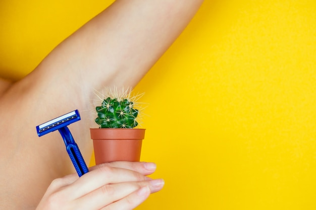 A woman holding a green cactus in a brown pot and a razor near the armpits. the concept of depilation, hair removal and removal unwanted hair on the body.
