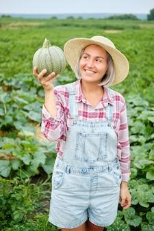 Женщина, держащая зеленую свежую тыкву на поле растений. красивая молодая девушка с здоровой овощной едой, стоя на ферме в солнечный теплый день. культивирование веганская культура органический природный продукт