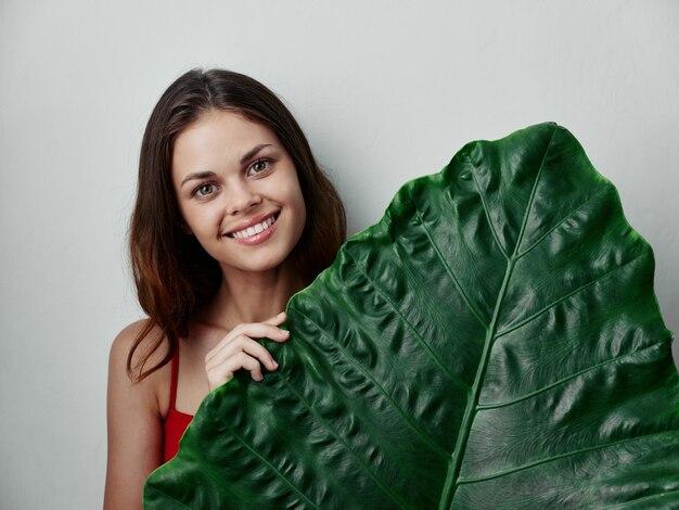 Женщина держит зеленый лист в руках улыбается привлекательный взгляд изолированный фон
