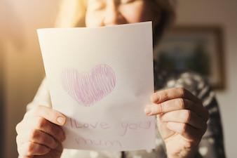グリーティングカードを持っている女性私はあなたを愛してお母さん碑文