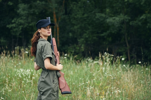 Woman holding a gun in his hands black cap travel lifestyle green overalls