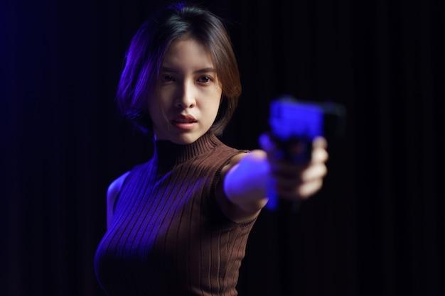 Женщина держит пистолет в темноте