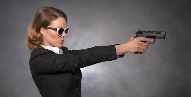 Woman holding gun with both hands and aiming at target Premium Photo