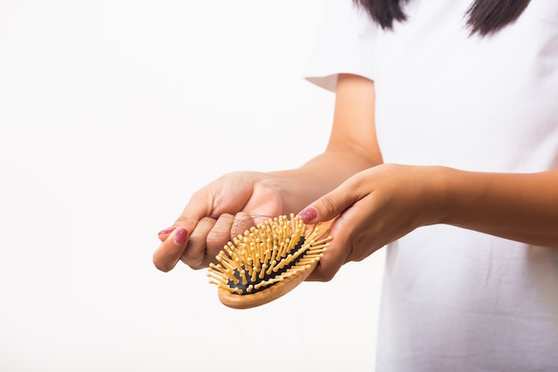 Woman holding hairbrush with damaged long